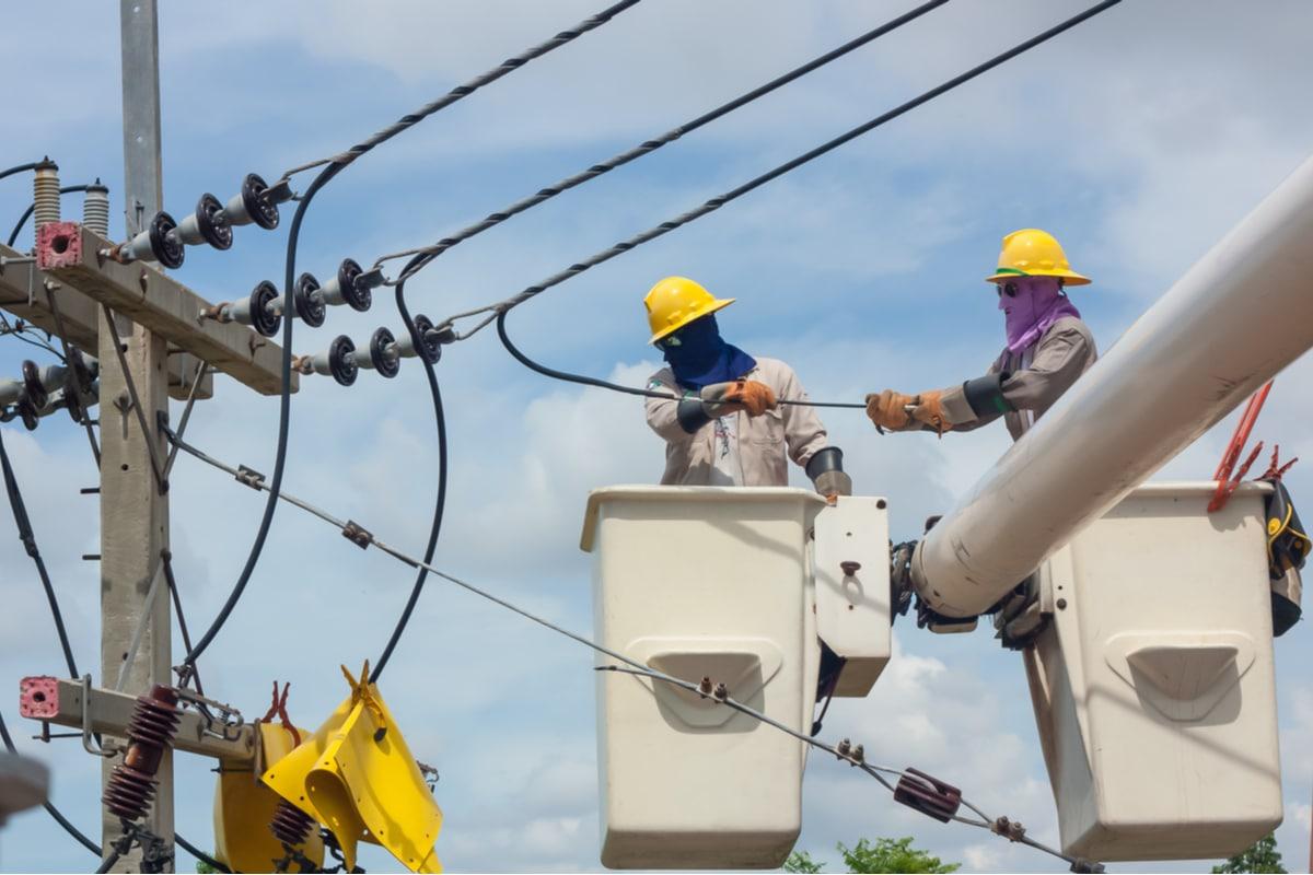 Utility workers in bucket truck fixing power lines